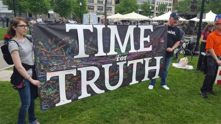 "people holding ""time for truth"" banner"
